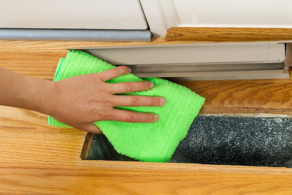 Person wiping inside of air vent duct with bright green towel