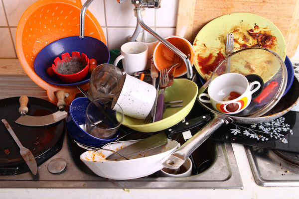 Dirty dishes piled high in a sink
