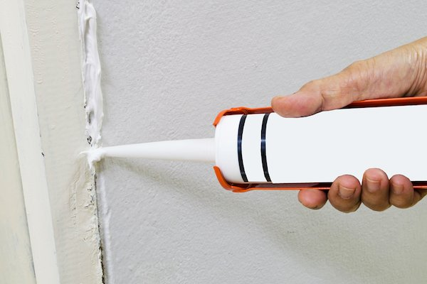 sealing a crack in a wall with caulk